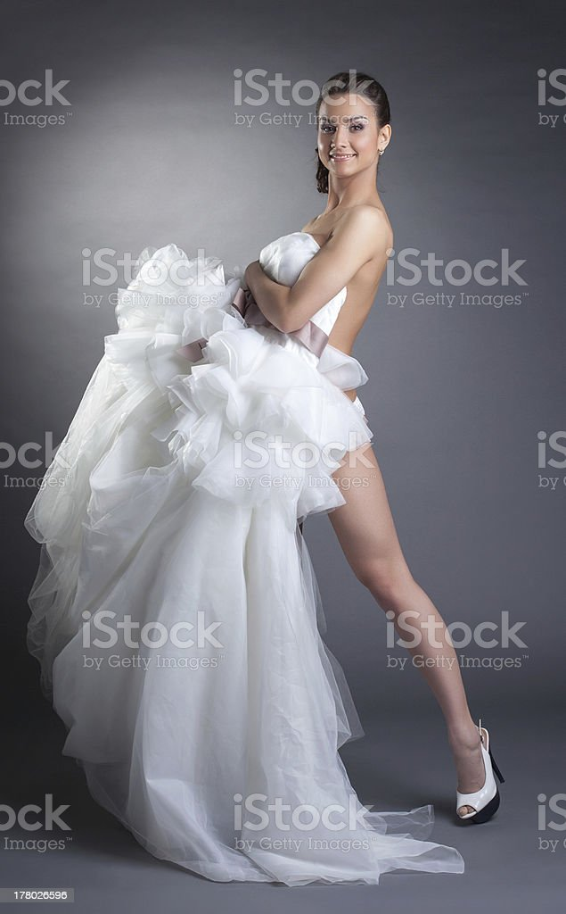 Smiling naked model covered by wedding dress royalty-free stock photo