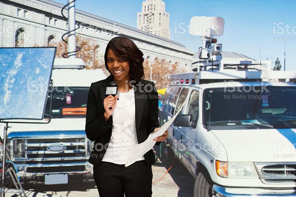 Smiling newscaster presenting news outdoors stock photo
