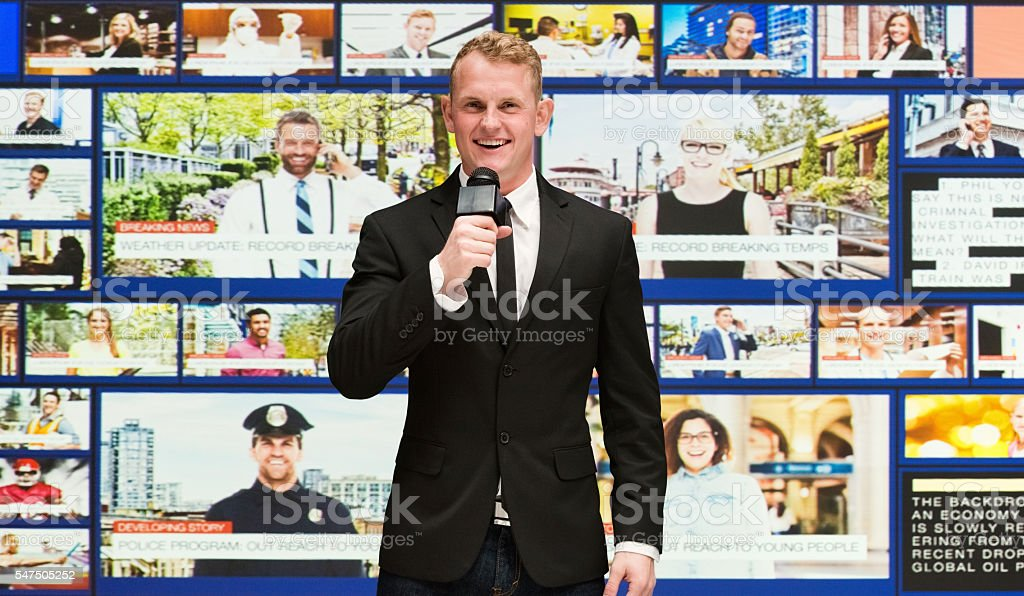 Smiling newscaster presenting news with microphone stock photo