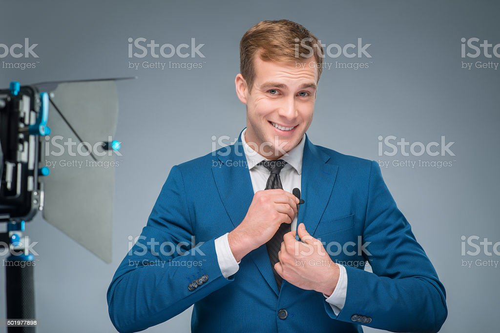 Smiling newsman adjusting the microphone stock photo