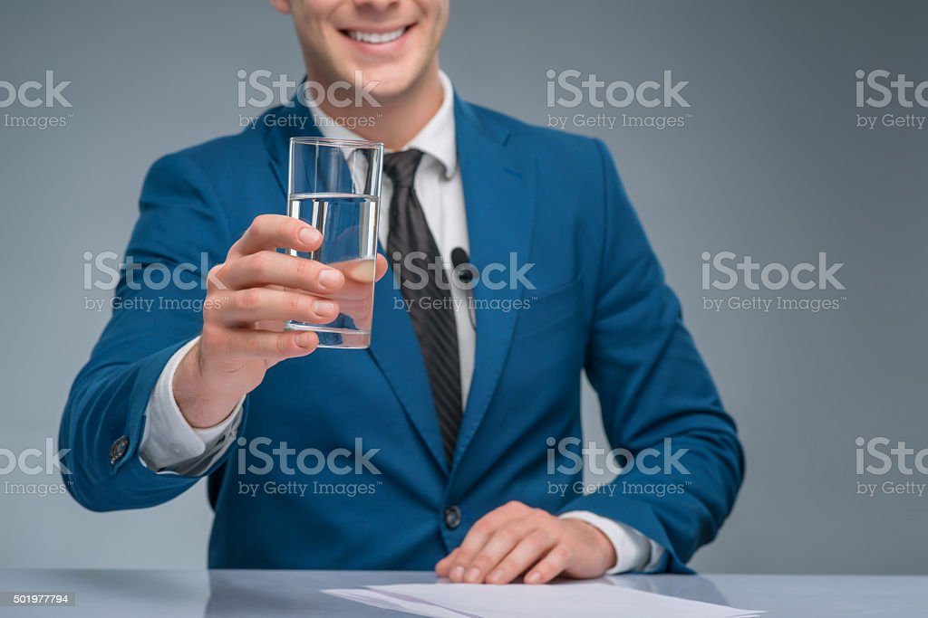 Smiling newsman holding a glass of water stock photo