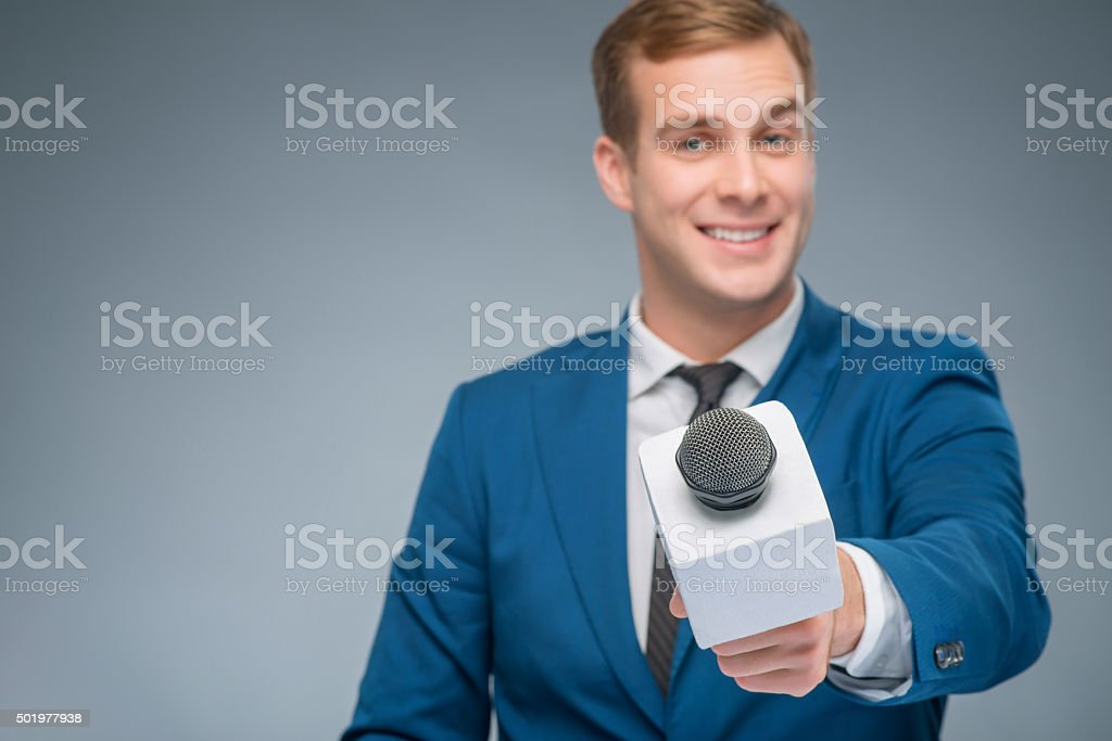 Smiling newsman taking an interview stock photo
