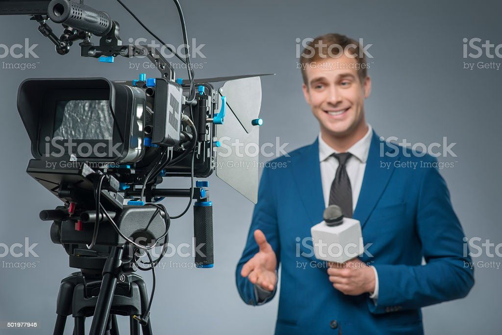Smiling newsman with a microphone stock photo