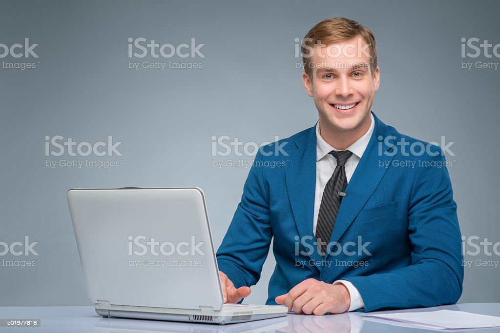 Smiling newsman working with his laptop stock photo