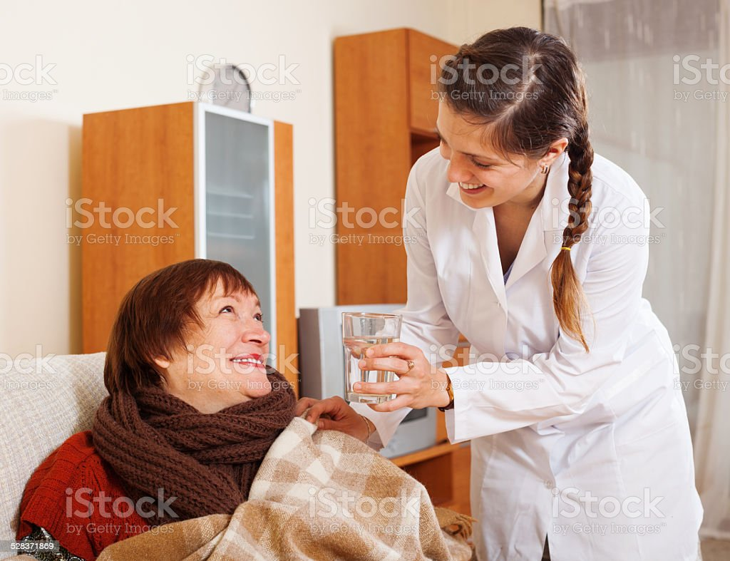 Smiling nurse in uniform caring for happy mature woman stock photo