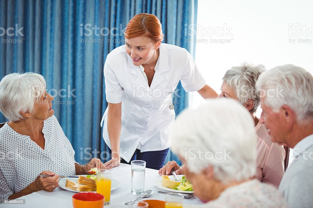 Smiling nurse looking at senior person during breakfast stock photo