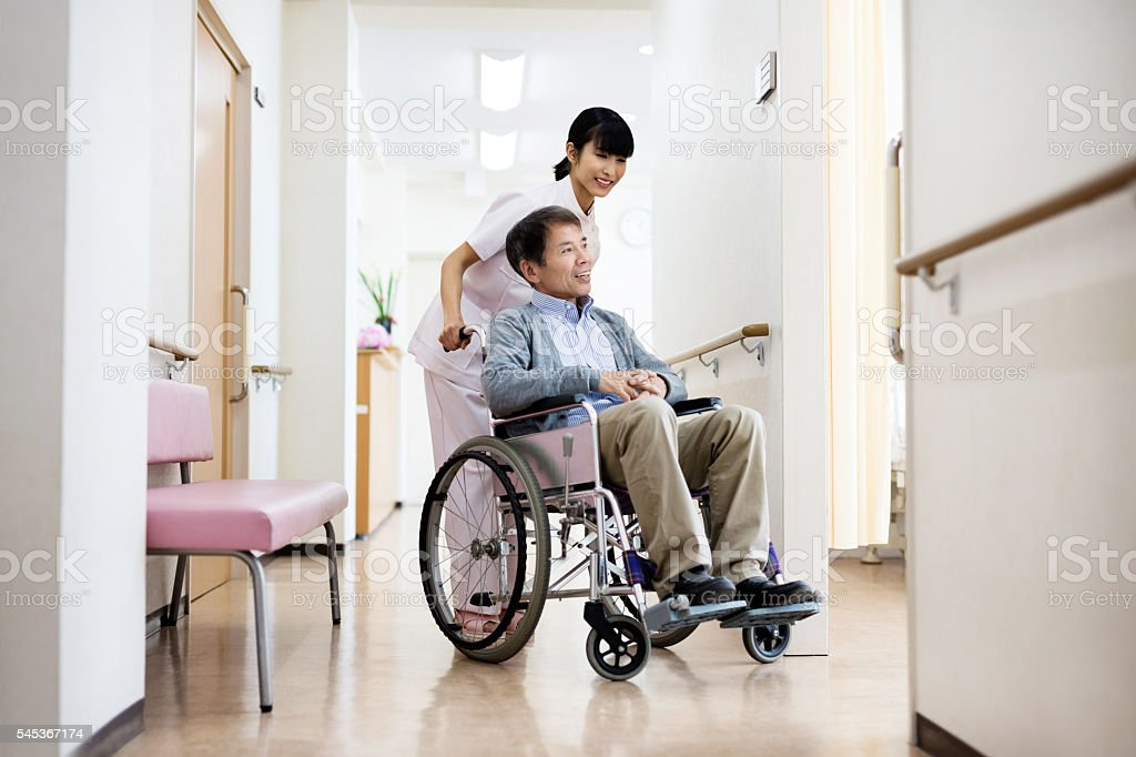 Smiling nurse pushing senior man sitting on wheelchair at hospit stock photo