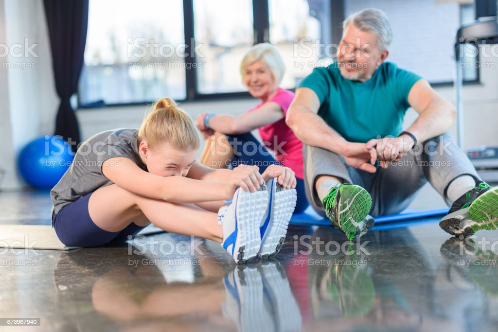 Smiling old couple and girl stretching in fitness class for kids and senior people stock photo