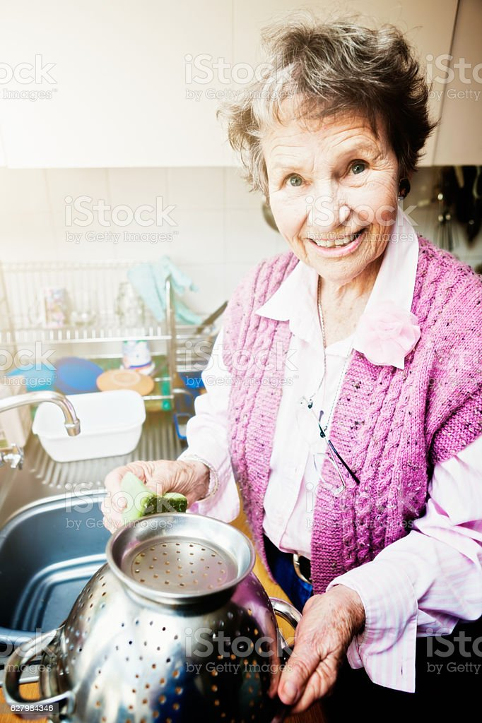 Smiling old lady busy with chores in her sunlit kitchen stock photo