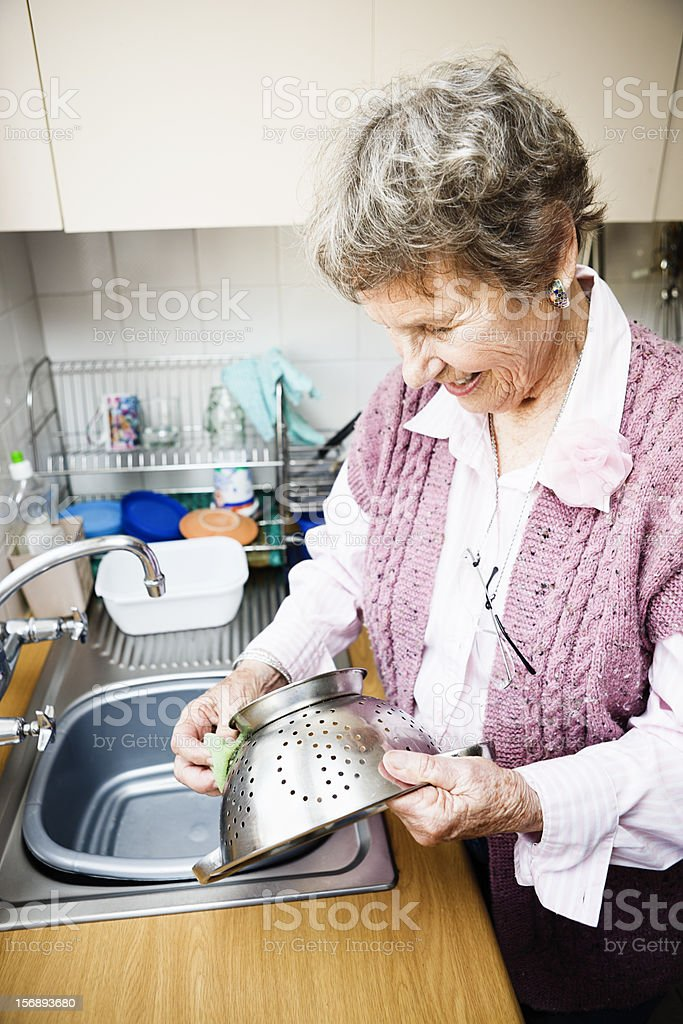 Smiling old lady washes a colander at kitchen sink royalty-free stock photo