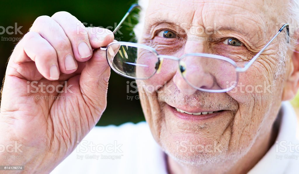 Smiling old man, vision corrected, looks over his spectacles stock photo