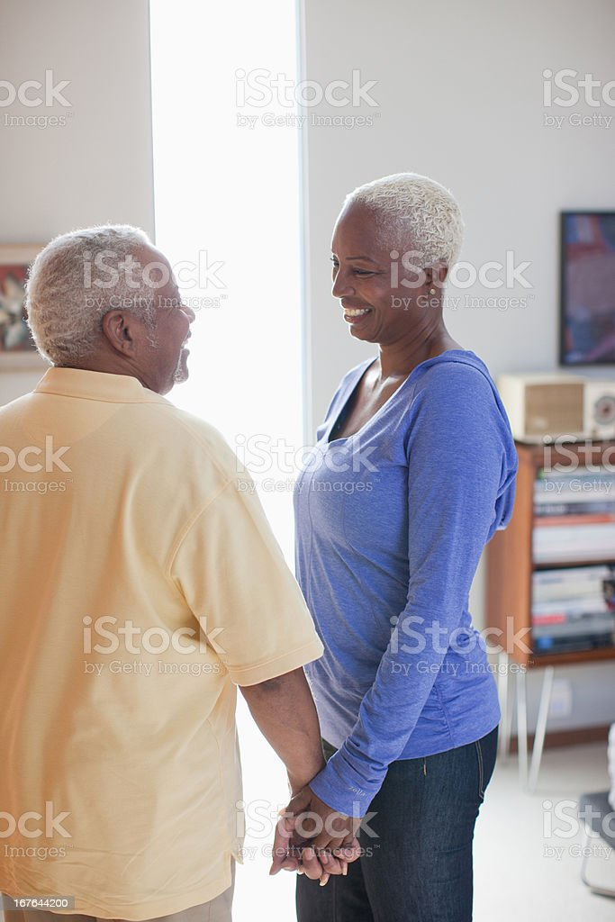 Smiling older couple holding hands indoors royalty-free stock photo