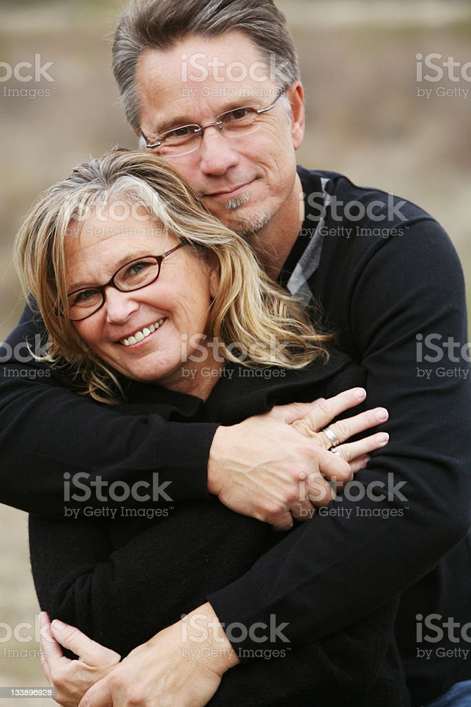 Smiling older couple in affectionate embrace royalty-free stock photo