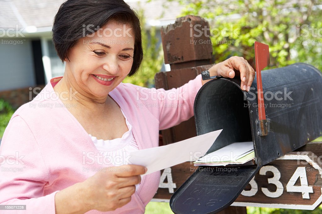 Smiling older Hispanic woman checking her mailbox stock photo