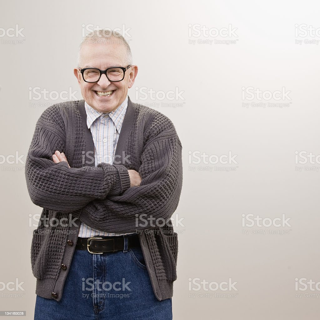 Smiling older man in sweater with arms crossed stock photo
