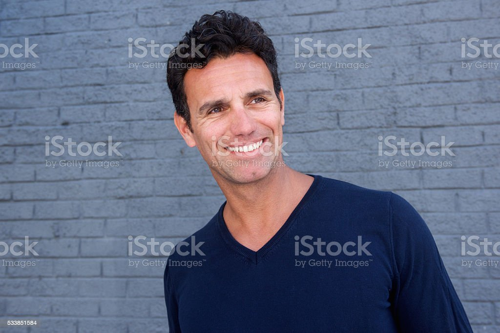 Smiling older man standing against gray wall stock photo