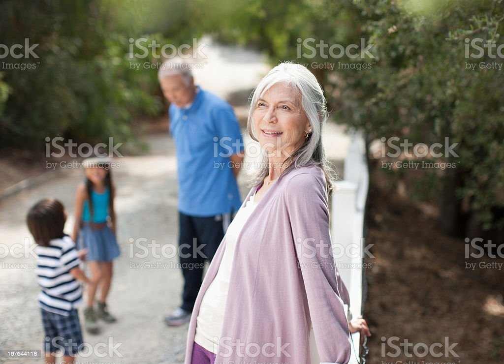 Smiling older woman standing outdoors stock photo