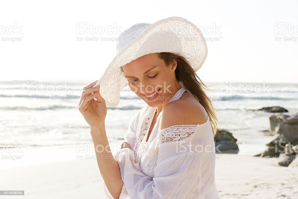 Smiling older woman with hat at the beach stock photo