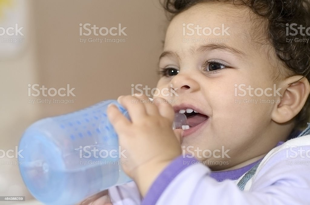 Smiling One Year Old Baby Girl Drinking Her Bottle royalty-free stock photo