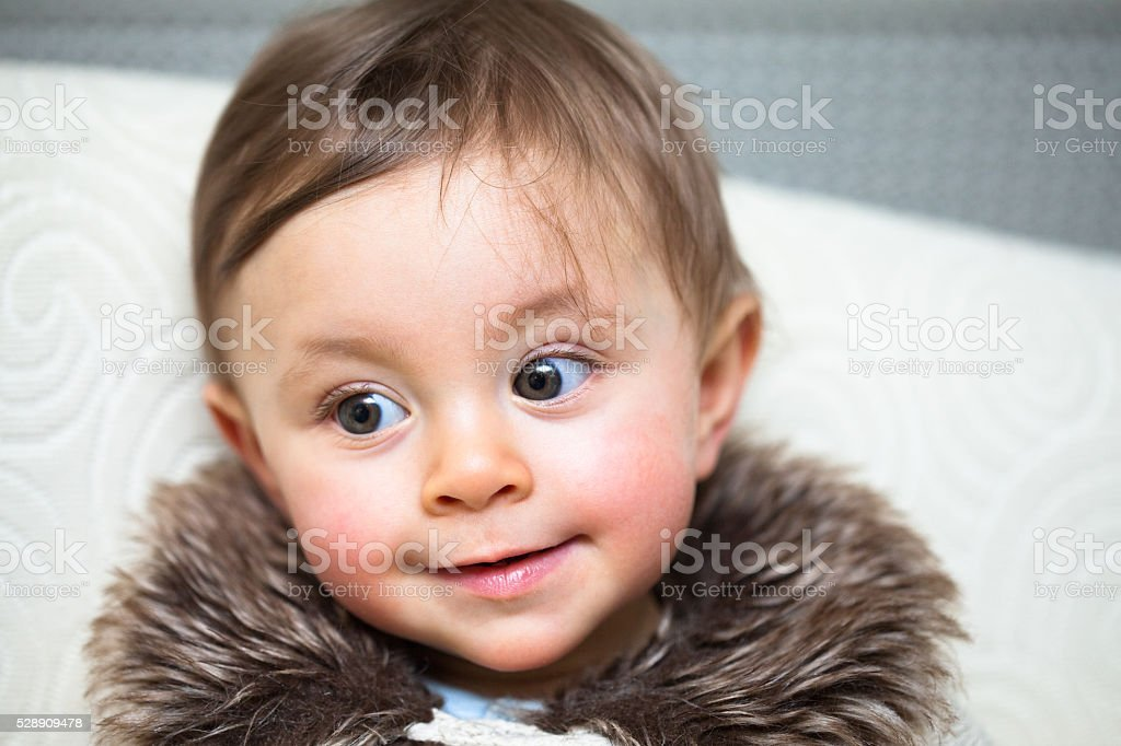Smiling one year old girl with a faux fur collar stock photo
