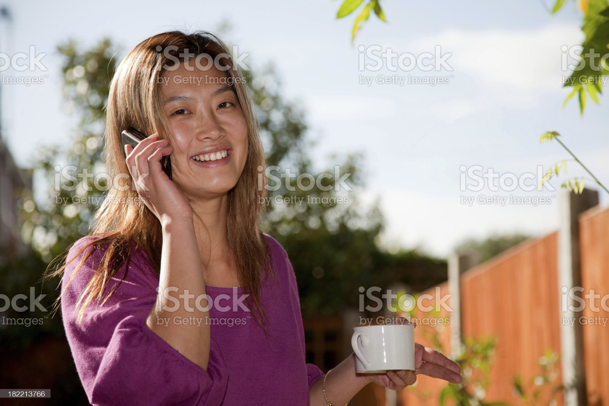 Smiling oriental asian woman on cellphone royalty-free stock photo