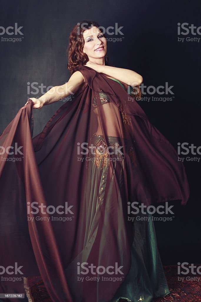 Smiling oriental dancer holding a silk cape royalty-free stock photo