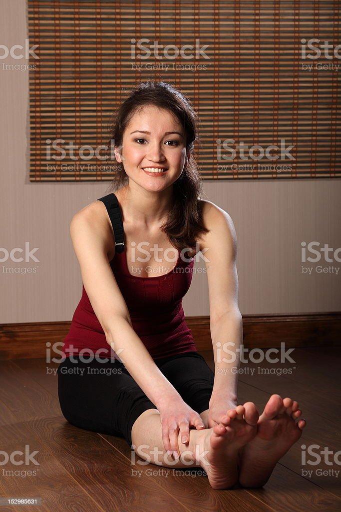 Smiling oriental girl sitting on floor doing fitness exercise royalty-free stock photo