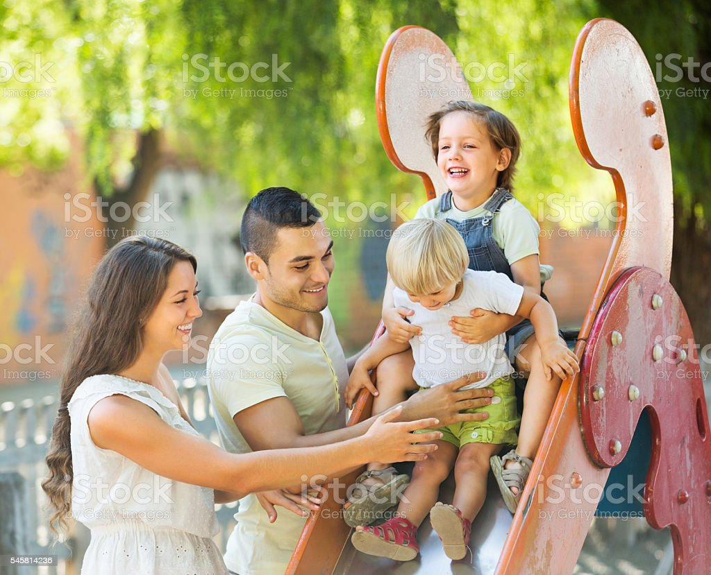 Smiling parents helping kids on slide stock photo