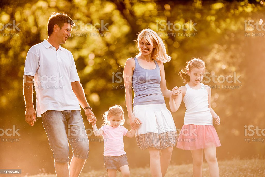 Smiling parents taking a walk with their daughters in nature. stock photo