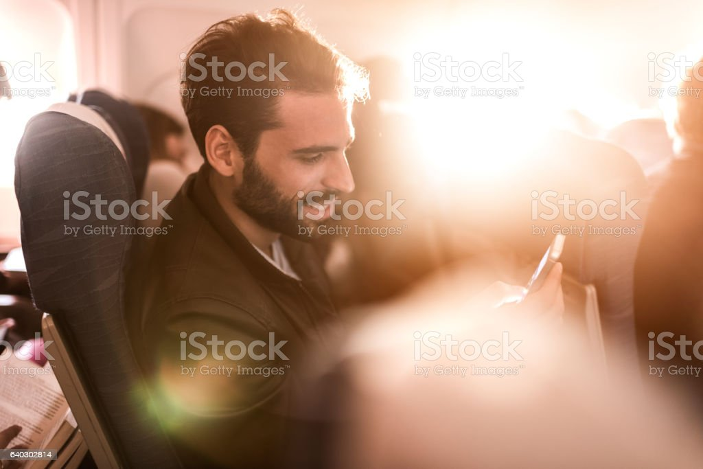 Smiling passenger text messaging on cell phone in the airplane. stock photo