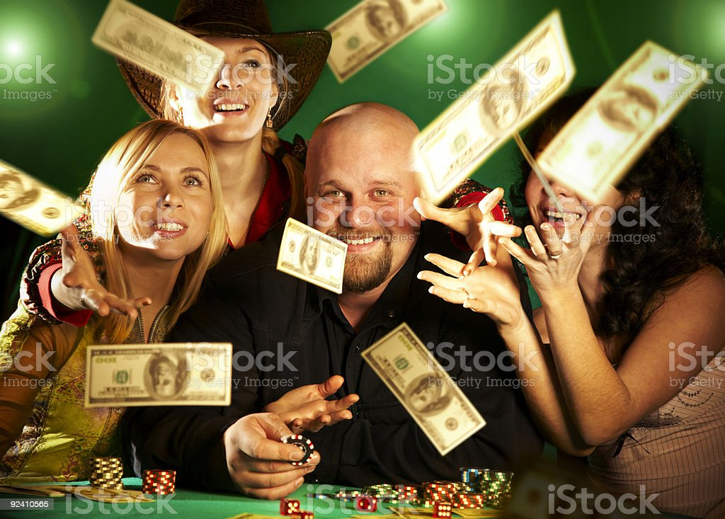 Smiling people at a poker table with money flying in the air royalty-free stock photo