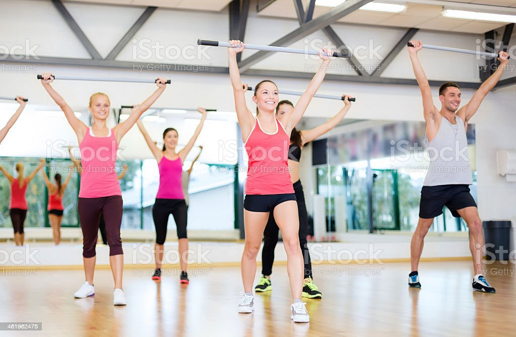 Smiling people in mirrored room working out with barbells stock photo
