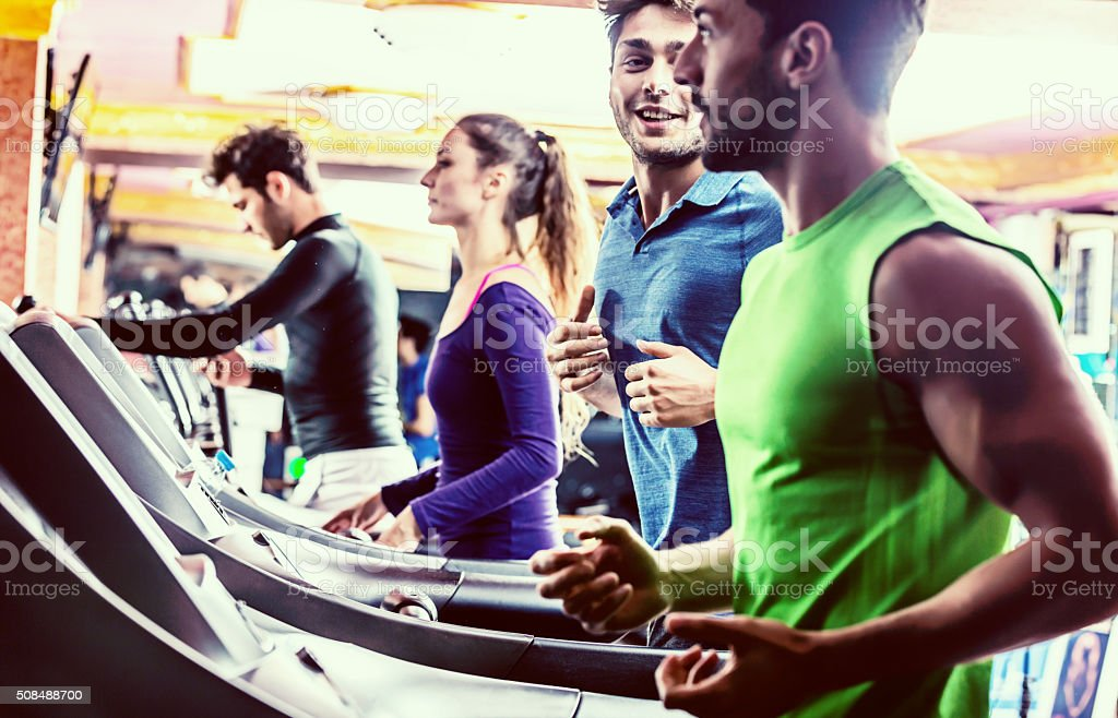 Smiling People Running on Treadmills in Gym stock photo