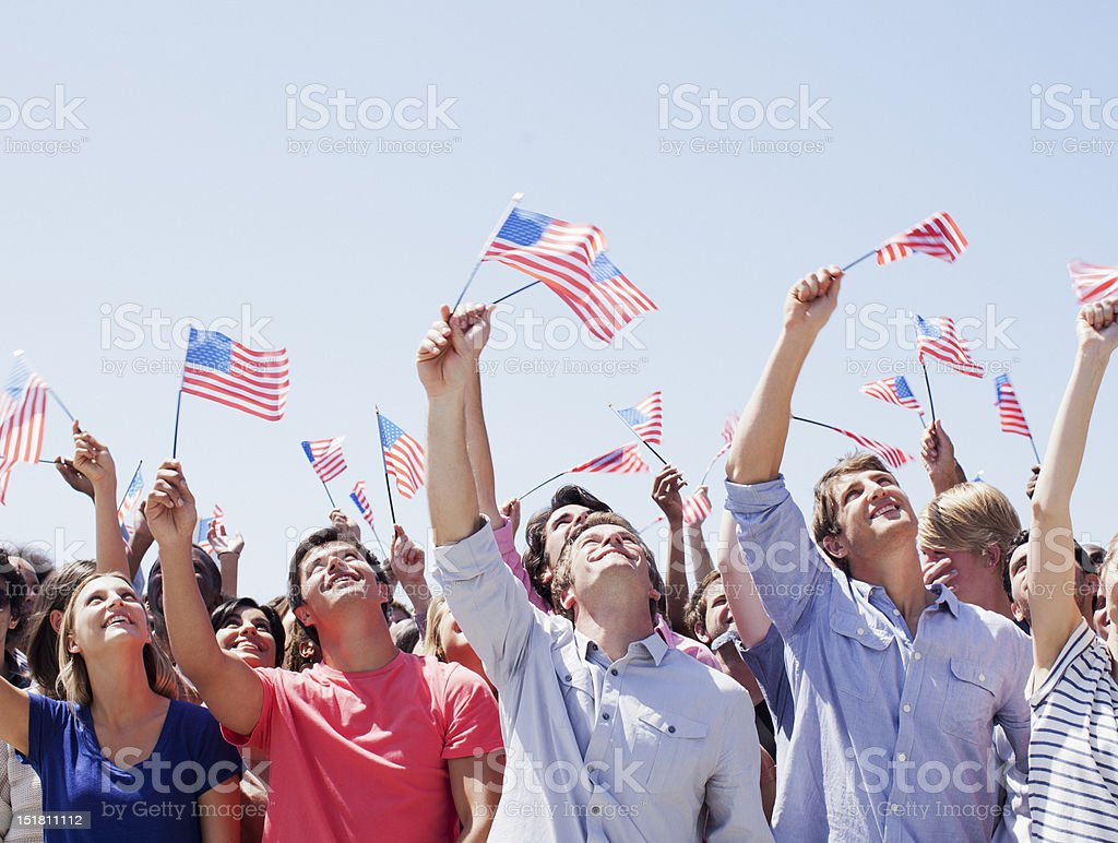 Smiling people waving American flags and looking up in crowd stock photo
