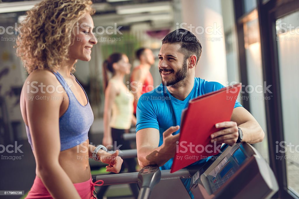 Smiling personal trainer assisting young woman in gym. stock photo
