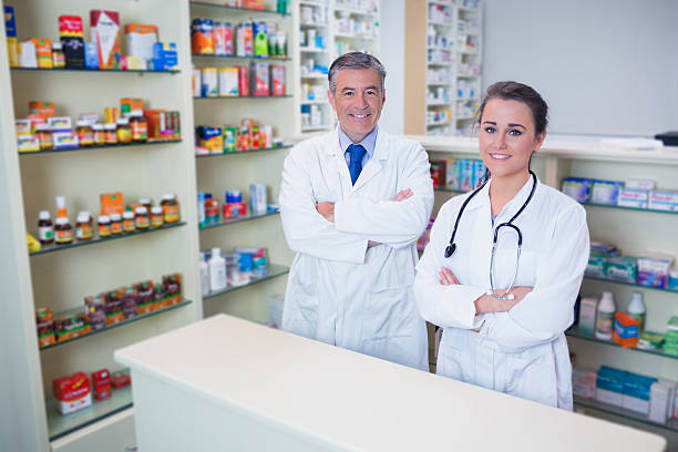 smiling pharmacist and his trainee with arms crossed stock photo - Pharmacist Trainee