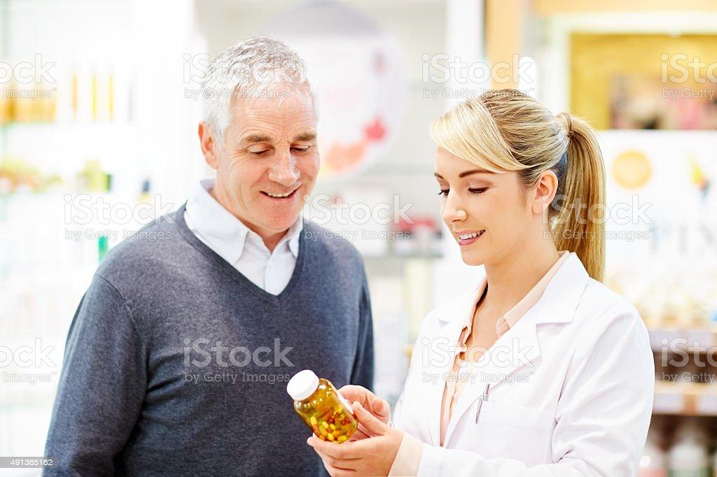 Smiling pharmacist explaining prescription to customer stock photo