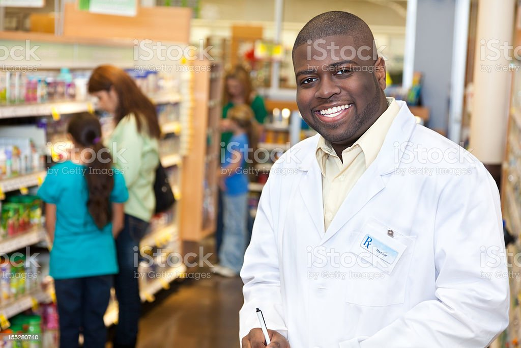 Smiling pharmacist in front of pharmacy aisle royalty-free stock photo