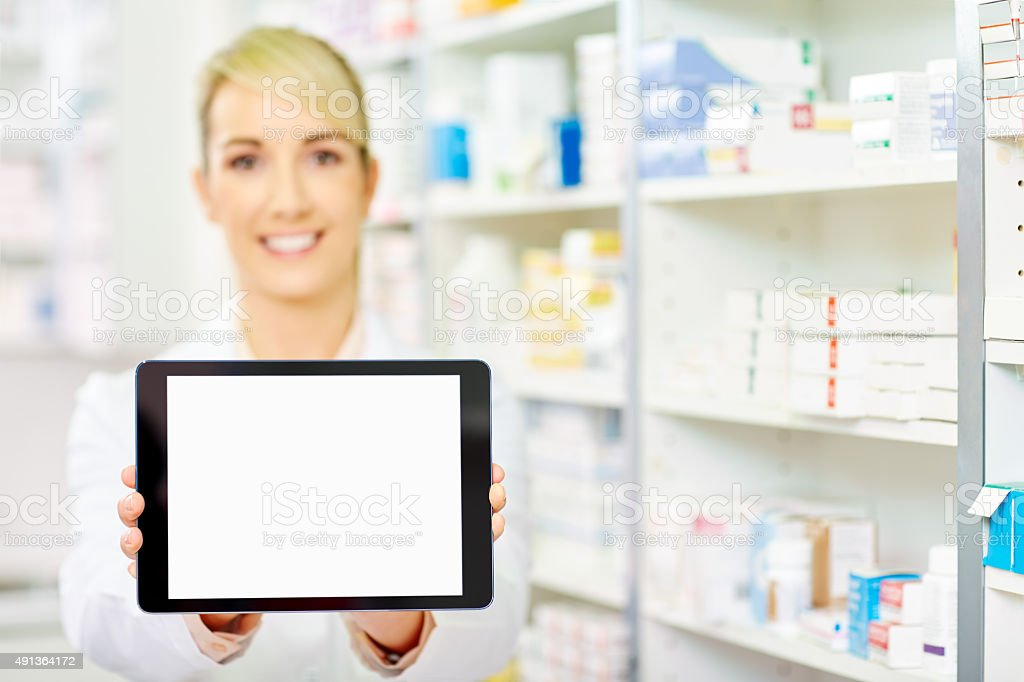 Smiling pharmacist showing tablet computer with blank screen stock photo
