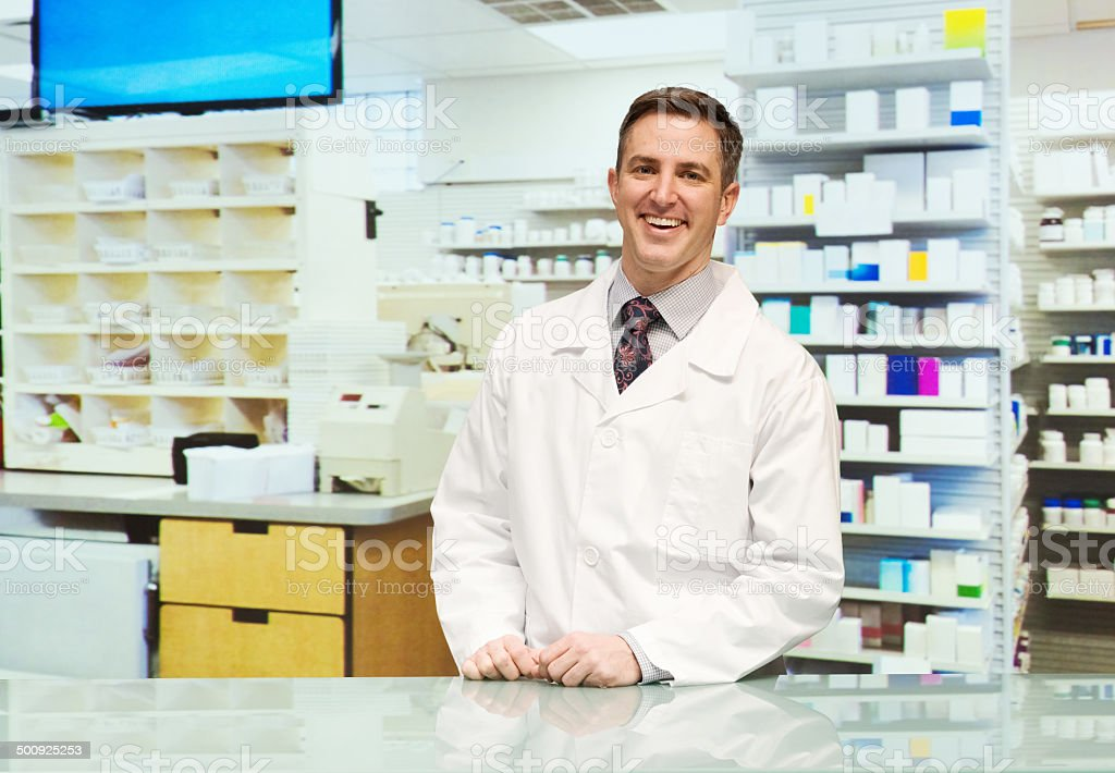 Smiling pharmacist standing pharmacy royalty-free stock photo