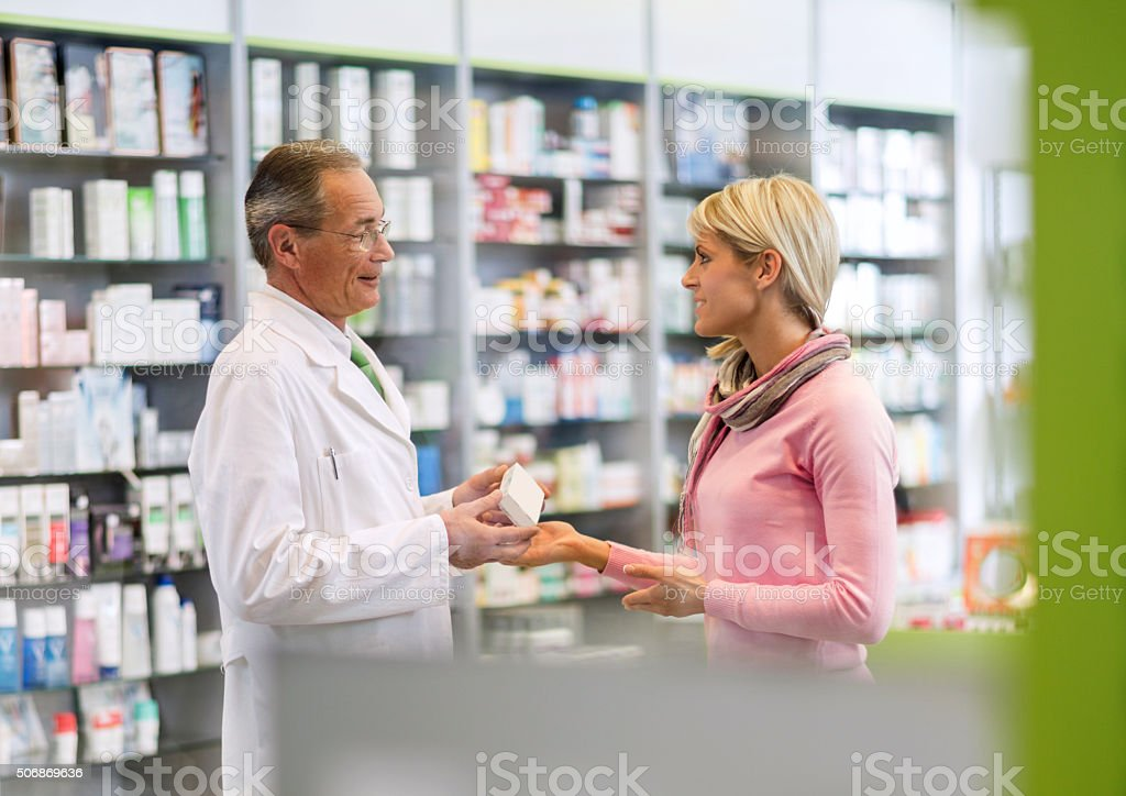 Smiling pharmacist talking young woman in a pharmacy. stock photo