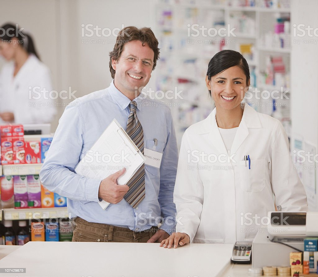 Smiling pharmacists in drug store standing at cash register stock photo