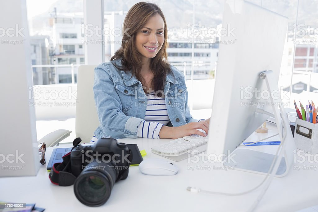 Smiling photo editor working on computer royalty-free stock photo