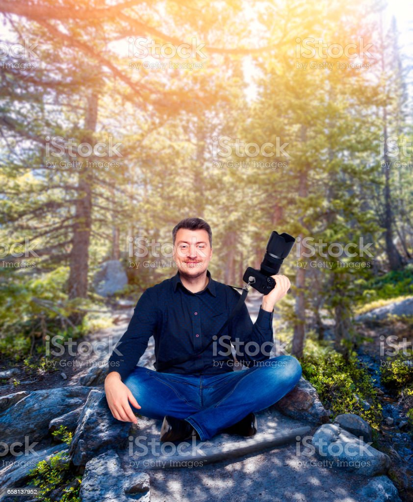 Smiling photographer with camera in yoga pose stock photo