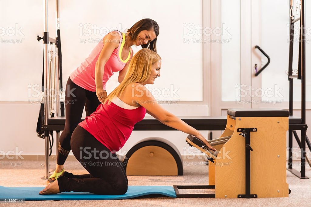 Smiling Pilates instructor assisting to pregnant woman during exercising. stock photo