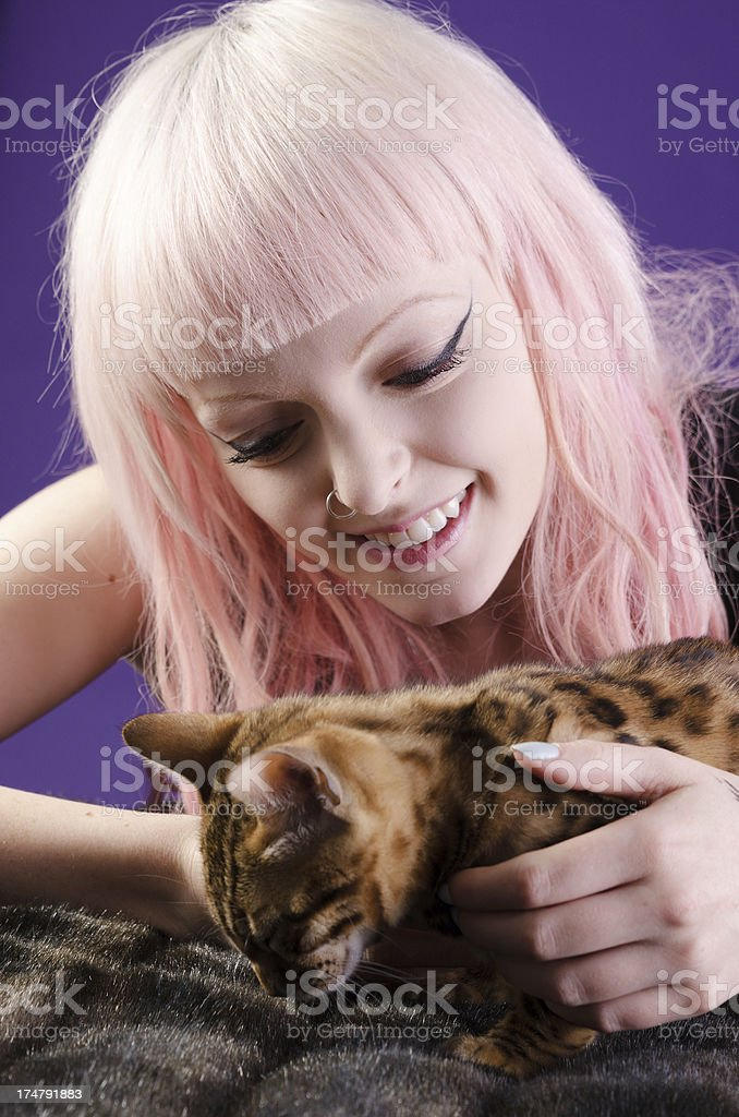 Smiling pink-haired woman bending over sleepy Bengal royalty-free stock photo