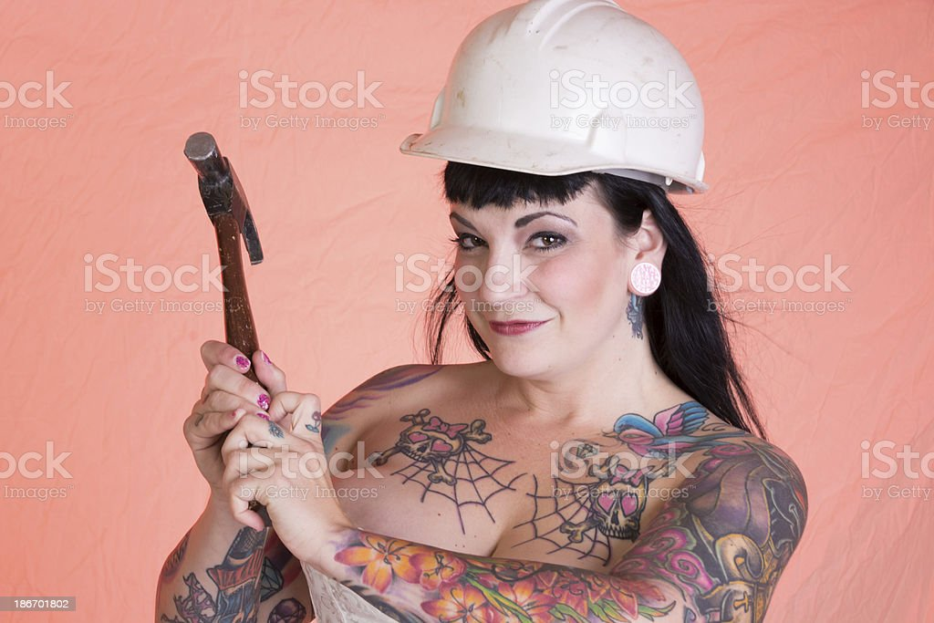 Smiling pinup model holding hammer with both hands. royalty-free stock photo