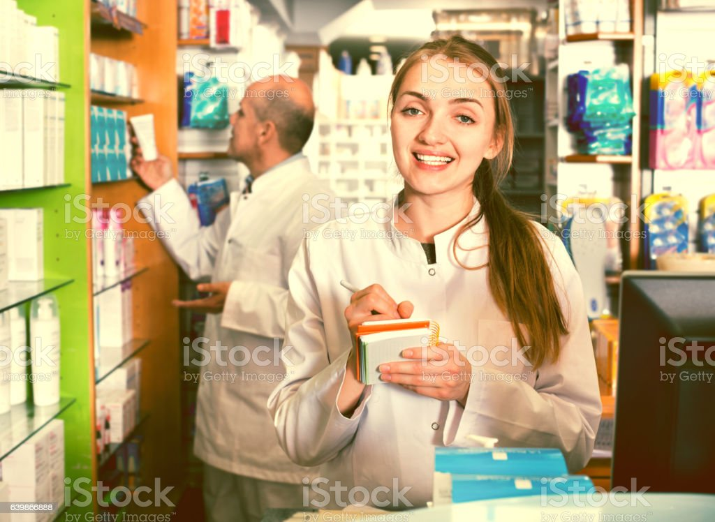 Smiling pleasant pharmacist and pharmacy technician stock photo