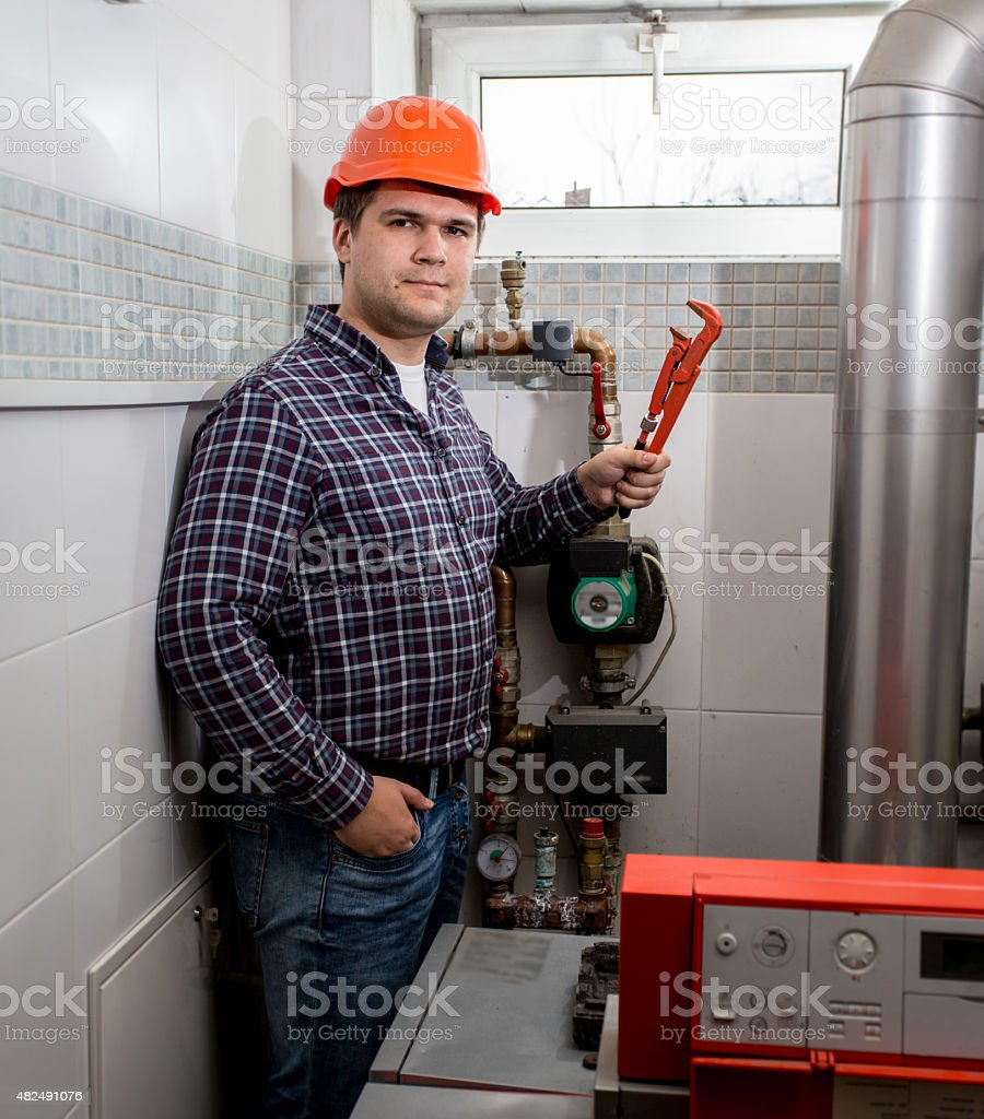 smiling plumber posing with pliers at boiler room stock photo