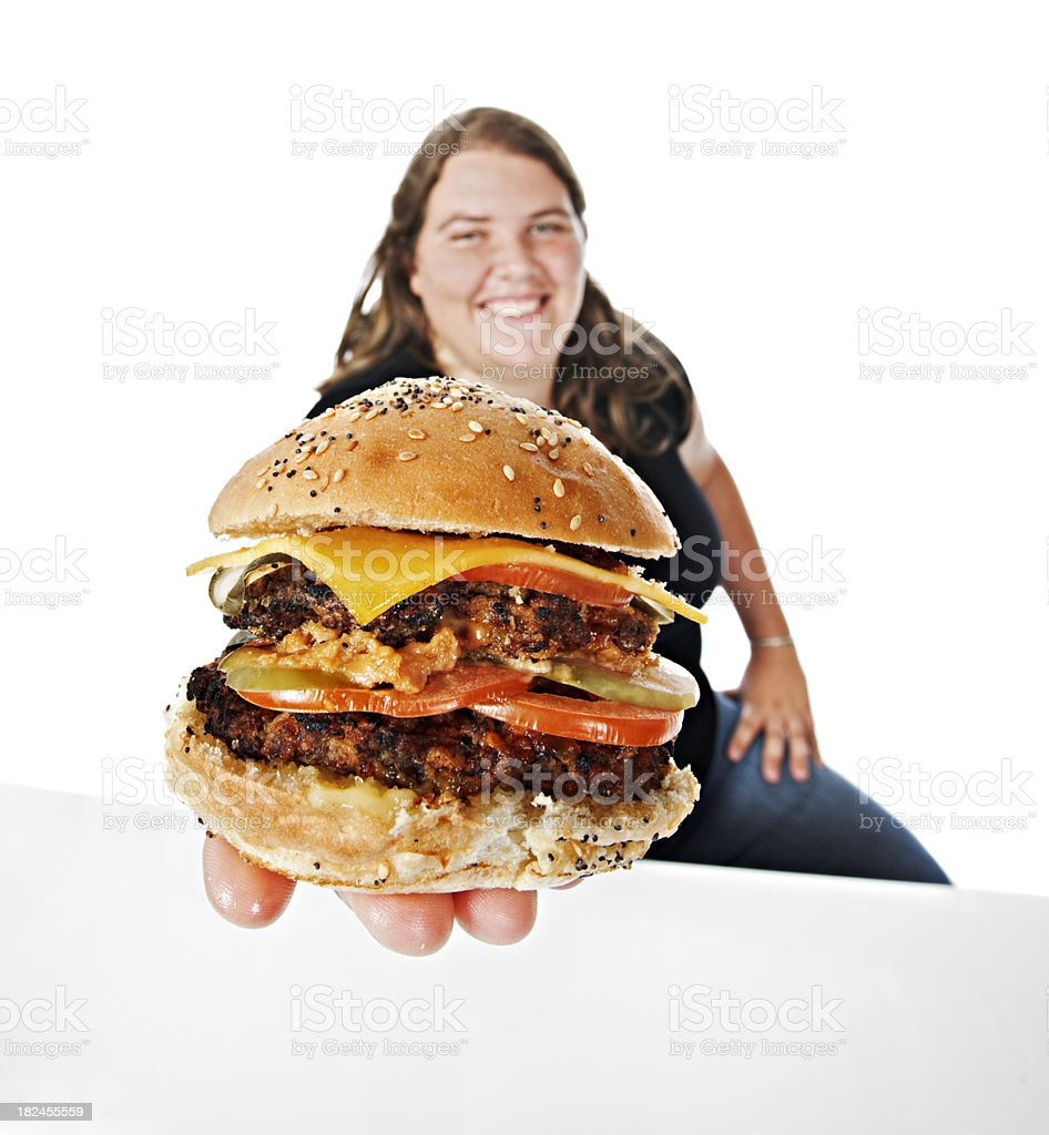 Smiling plump young woman offers cheeseburger to camera stock photo